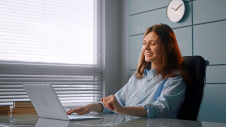 Smiling worker brunette with long loose hair types on grey laptop